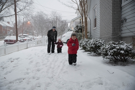 Family playing in snowy yard