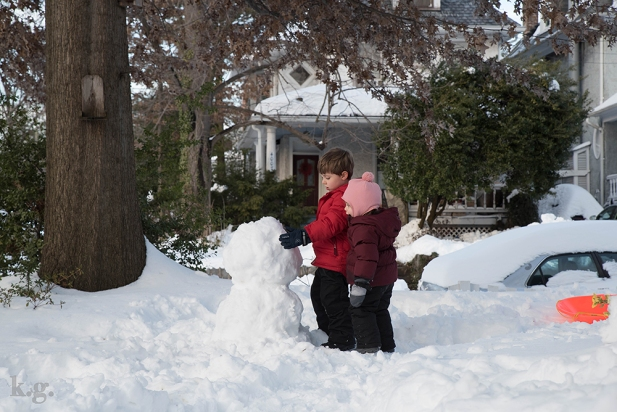 Two children building a snowman